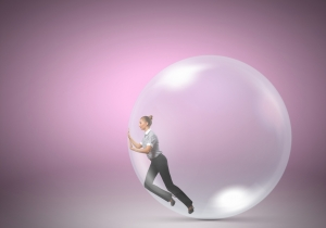 Young businesswoman trying to get out of soap bubble