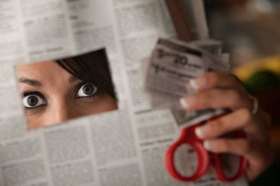 Lady cutting a coupon out of a newspaper