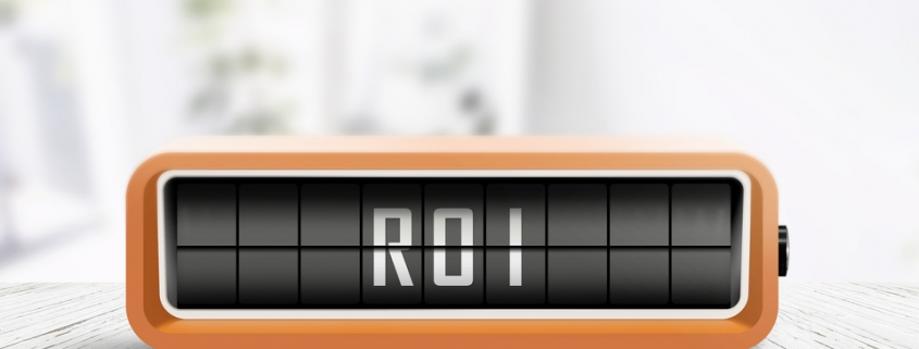 ROI sign and the abbreviation for return of investment in a bright room on a table