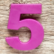 Purple number five on the wooden background