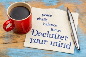 Declutter your mind for clarity - handwriting on a napkin with a cup of espresso coffee