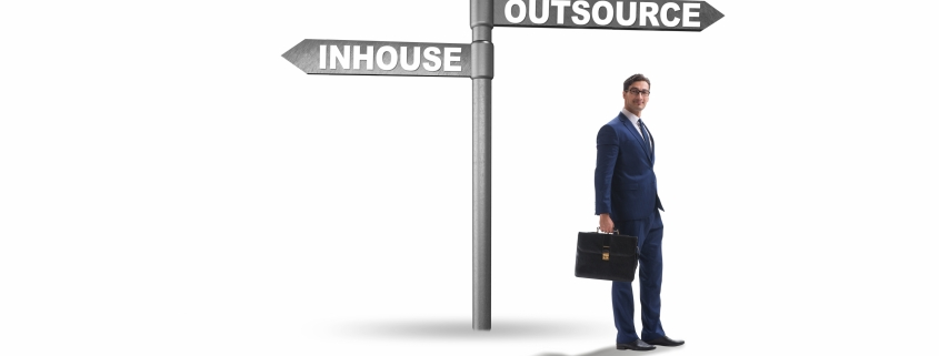 Businessman at crossroads deciding between outsourcing and inhouse