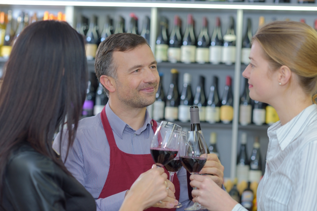 People sampling red wine in a store