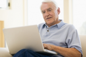 Ageing man in living room with laptop smiling